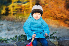 Portrait of adorable toddler boy with blue jacket and colorful u Stock Photos