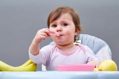 Adorable toddler girl is having fun while eating some fruits on greyish background. Portrait of adorable toddler girl having fun while eating friuts, sitting in stock images