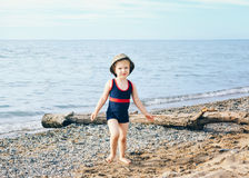 Portrait of adorable white Caucasian one toddler little girl with hat on her head going on lake sea gravel beach Royalty Free Stock Images