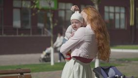 Portrait of adorable woman holding the baby in arms and smiling in the yard close-up. The lady enjoying the sunny day. Portrait of beautiful red-haired woman stock video footage