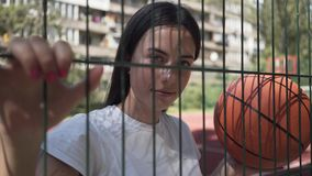Portrait of adorable woman holding basketball ball looking at the camera standing behind the mesh fence outdoors. Portrait of brunette woman with basketball ball stock video