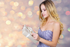 Portrait of an adorable woman opening present box Royalty Free Stock Image
