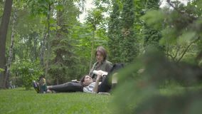 Portrait adorable young couple in casual clothes spending time together outdoors, having date. The guy sitting on the stock footage