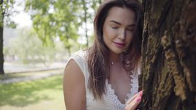Portrait adorable young girl with long brunette hair wearing a long white summer fashion dress standing next to a tree stock footage