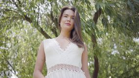 Portrait beautiful young girl with long brunette hair wearing a long white summer fashion dress standing under the stock video footage