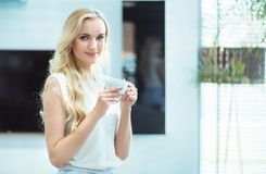 Portrait of an adorable young lady drinking coffee Stock Photos