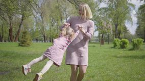Portrait adorable young mother spinning the daughter on hands on nature on spring day. Woman and kid playing in the park. Portrait young mother spinning the stock video