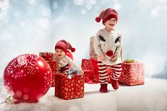 Portrait of adroable twin-elves among huge Christmas presents. Portrait of joyful twin-elves among huge Christmas presents stock images