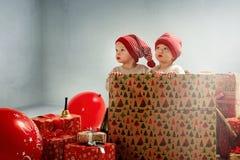 Portrait of adroable twin-elves among huge Christmas presents. Portrait of joyful twin-elves among huge Christmas presents stock photo