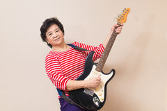 Portrait of adult asian woman with electric guitar, warm toned, Stock Image