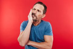Portrait of adult bearded man suffering from toothache and touch. Ing jawbone with pain on face isolated over red background Royalty Free Stock Image