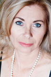 Portrait of adult blond woman. Vertical portrait blond woman with pearl beads Stock Image