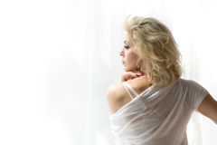 Portrait of adult blonde woman looking at window Royalty Free Stock Images