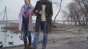 Portrait of adult Caucasian couple walking along riverbank and leaving. Ducks flying up from the shore. Nature, leisure