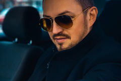 Portrait of adult caucasian male in coat and sunglasses. Looking Royalty Free Stock Images