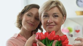 Portrait of adult daughter and mother holding tulips, celebrating Women Day