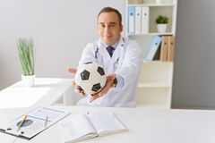 Portrait of adult doctor sitting at his desk Royalty Free Stock Image