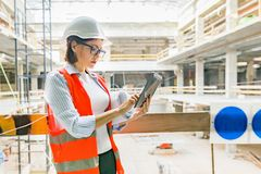Portrait of adult female builder, engineer, architect, inspector, manager at construction site. Woman with plan, digital tablet royalty free stock photo