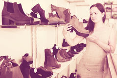 Portrait of adult female selecting loafers. In footgear center Stock Photography