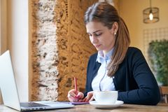 Portrait of adult female working in their business at a table in cafe making notes in a notebook over a Cup of coffee and laptop royalty free stock photo
