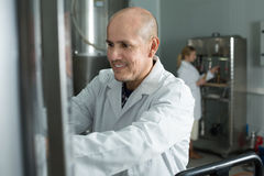 Portrait of adult glad male brewery worker. On beer production factory Royalty Free Stock Images