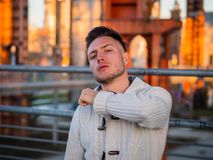 Confident young man doing threatening gesture to camera. Portrait of adult handsome man doing menacing gesture like cutting throat, with modern hairstyle wearing royalty free stock images