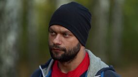 Portrait of adult handsome man at nature at autumn day, bearded guy is looking at camera calmly, closeup of face
