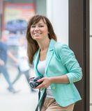 Portrait of adult happy pretty smiling caucasian woman photographer standing next to a wall on city street holding photo. Camera at summer day. Hobby or Stock Photography