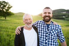 A portrait of an adult hipster son with senior father in nature at sunset, arms around each other. A portrait of a laughing adult hipster son with senior father royalty free stock photos