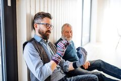 Portrait of adult hipster son and senior father sitting on floor indoors at home, having fun. royalty free stock images