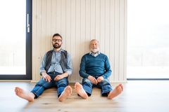 A portrait of adult hipster son and senior father sitting on floor indoors at home. stock photo