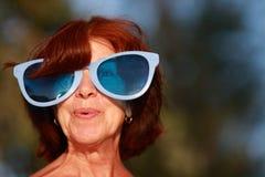 Portrait of an adult lady in amusing big blue glasses. Joyful, surprised Stock Image