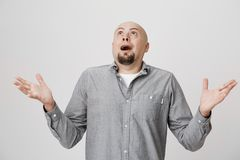 Portrait of an adult man looking up in the sky with surprised or shocked expression over white background. Person. Spreads his hands not having clue of what is Stock Photos