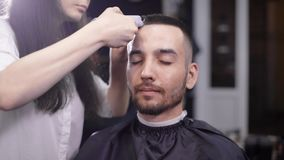 Portrait of an adult man who is done with trimming hair in a man`s beauty salon, the hairdresser neatly chooses his hair stock video footage