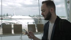 Portrait of adult man, who is using his smartphone in the airport. Male traveller is standing in the airport, near big window with a nice view to airside with stock footage