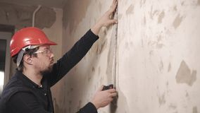Portrait of the steward, worker measures the centimeter length of the wall stock video
