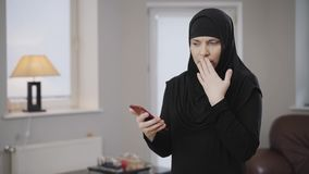 Portrait of adult muslim woman scrolling on smartphone with displeased facial expression. Lady in hijab expressing