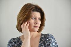 Portrait of adult sad female on light background Stock Photo