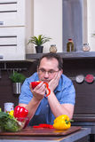 Portrait of adult sad man cooking in the kitchen Stock Images