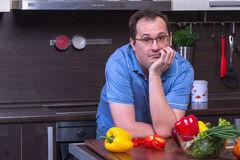 Portrait of adult sad man cooking in the kitchen Royalty Free Stock Image