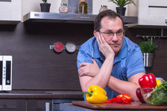 Portrait of adult sad man cooking in the kitchen Royalty Free Stock Photography