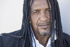 Portrait of adult strong black men with long dreadlocks and blue eyes. Serious kind man in a classic style - white shirt, blazer. This Dominican man works as a Royalty Free Stock Image
