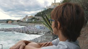 Portrait of adult woman with eyeglasses and red hairs. Waving ocean defocused in the background. stock video