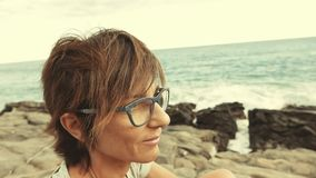 Portrait of adult woman with eyeglasses and red hairs. Waving ocean defocused in the background. stock video footage