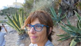 Portrait of adult woman with eyeglasses and red hairs. Waving ocean defocused in the background. stock footage