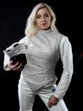 Portrait of adult woman fencer. Holding training mask and rapier. Olympic sports, martial arts and professional training concept Stock Photography