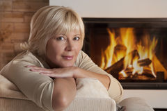 Portrait of adult woman near fireplace Stock Photography