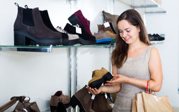 Portrait of adult woman selecting loafers. In footgear center Royalty Free Stock Images