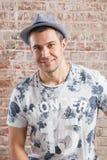 Portrait adulte à la mode d'homme sur le mur de briques de fond image stock