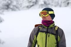 Portrait of adventurer in goggles during a winter travel. In wilderness, on blurred background Stock Image